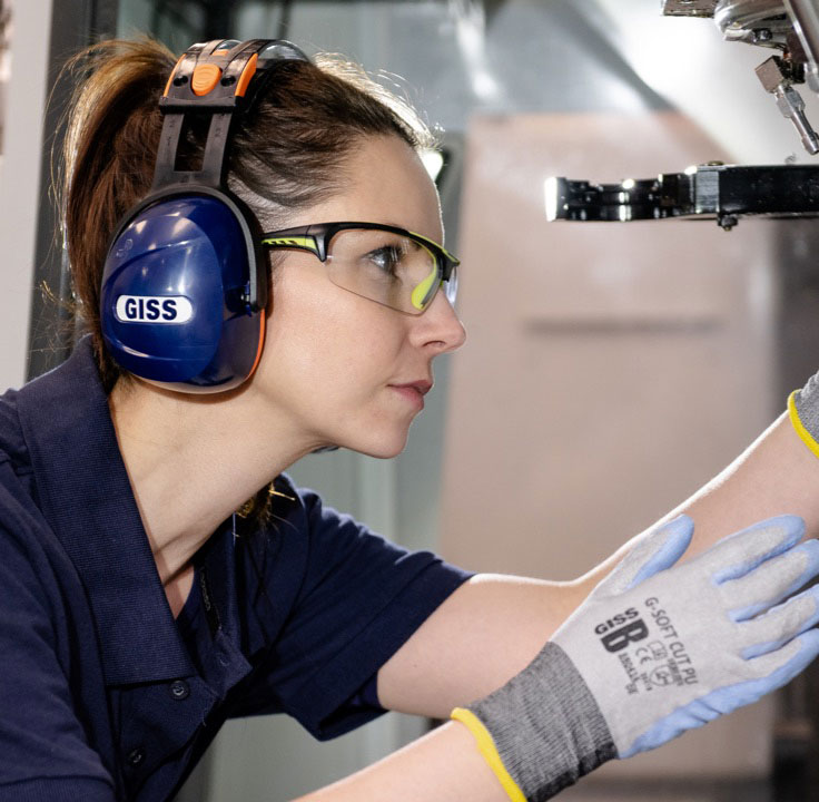 A woman is wearing GISS headphones for ear protection.